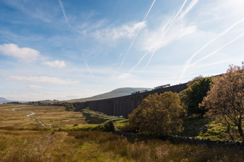 A goods train crossing Ribblehead viaduct with Park Fell in the background.