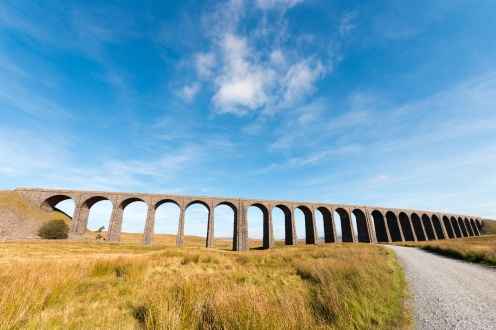 Ribblehead Viaduct lit up by the sun.