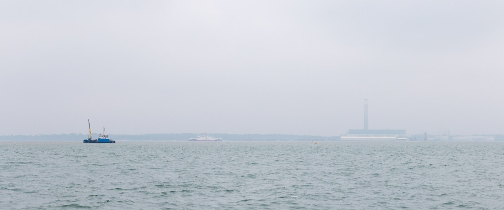 Fawley Power Station through the mist and drizzle hanging over the sea.